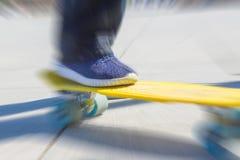 Un adolescente monta en un pennyboard amarillo Acción radial de la falta de definición del enfoque Fotos de archivo