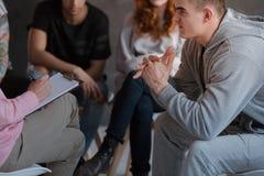 Un adolescente nervoso che si siede davanti ad un terapista immagini stock