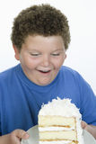 Un adolescente obeso que mira la torta Fotos de archivo