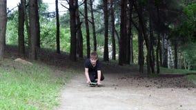 Un adolescente pattina su un pattino con uno scorrevole nel parco della città