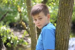Un adolescente presenta para un fotógrafo mientras que camina en el parque Imágenes de archivo libres de regalías