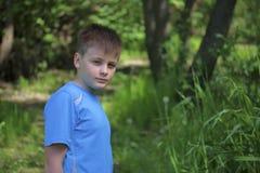 Un adolescente presenta para un fotógrafo mientras que camina en el parque Foto de archivo