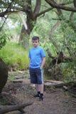 Un adolescente presenta para un fotógrafo mientras que camina en el parque Imagenes de archivo