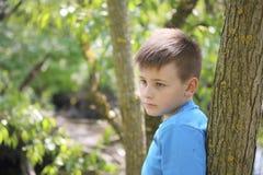 Un adolescente presenta para un fotógrafo mientras que camina en el parque Mirada pensativa Foto de archivo