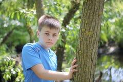 Un adolescente presenta para un fotógrafo mientras que camina en el parque Mirada pensativa Fotografía de archivo