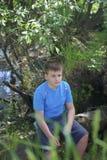 Un adolescente presenta para un fotógrafo mientras que camina en el parque Mirada pensativa Imágenes de archivo libres de regalías