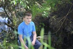 Un adolescente presenta para un fotógrafo mientras que camina en el parque Mirada pensativa Fotos de archivo