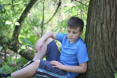 Un adolescente presenta para un fotógrafo mientras que camina en el parque Se sienta, inclinándose en un árbol Fotografía de archivo libre de regalías