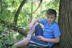 Un adolescente presenta para un fotógrafo mientras que camina en el parque Se sienta, inclinándose en un árbol Fotografía de archivo