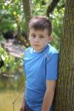 Un adolescente presenta para un fotógrafo mientras que camina en un parque por el río Imágenes de archivo libres de regalías