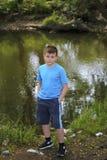 Un adolescente presenta para un fotógrafo mientras que camina en un parque por el río Fotos de archivo libres de regalías
