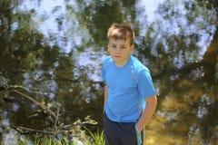 Un adolescente presenta para un fotógrafo mientras que camina en un parque por el río Imagen de archivo