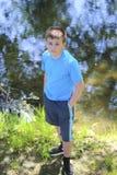Un adolescente presenta para un fotógrafo mientras que camina en un parque por el río Imagenes de archivo
