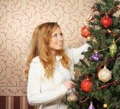 Un adolescente que adorna el árbol de navidad Foto de archivo