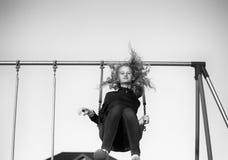 Un adolescente que balancea en un oscilación Imagen de archivo libre de regalías