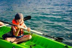 Un adolescente que bate un kajak en un lago Hay trole en el kajak con él Foto de archivo libre de regalías