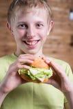 Un adolescente que come un bocadillo Fotografía de archivo libre de regalías