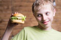 Un adolescente que come un bocadillo Fotos de archivo