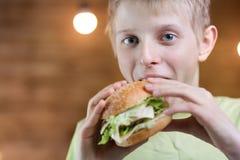 Un adolescente que come un bocadillo Imagen de archivo