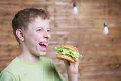 Un adolescente que come un bocadillo Imagenes de archivo