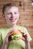 Un adolescente que come un bocadillo Imagen de archivo libre de regalías