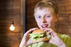 Un adolescente que come un bocadillo Foto de archivo