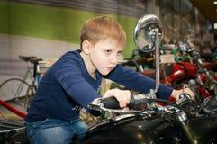 Un adolescente que conduce una motocicleta Imágenes de archivo libres de regalías