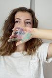 Un adolescente que cubrirá la parte de la cara con un pintado a mano Fotografía de archivo libre de regalías