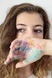 Un adolescente que cubrirá la parte de la cara con un pintado a mano Fotos de archivo
