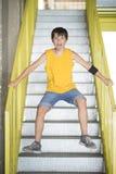 Un adolescente que salta en las escaleras y la sonrisa Fotografía de archivo