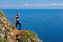 Un adolescente que se coloca en la orilla del lago Baikal Foto de archivo libre de regalías