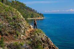 Un adolescente que se coloca en una colina en el lago Baikal Fotografía de archivo
