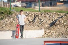 Un adolescente que se opone en un skatepark en una camiseta gris con un monopatín a disposición al contexto de las cercanías de Imágenes de archivo libres de regalías