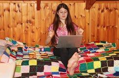 Un adolescente que se sienta en su cama y que trabaja en su ordenador portátil Imagen de archivo libre de regalías