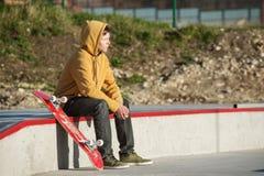 Un adolescente que se sienta en una sudadera con capucha amarilla con un monopatín contra un fondo de tugurios de la ciudad urban Fotos de archivo libres de regalías
