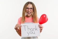 Un adolescente que sostiene un papel con un agradecimiento usted para mandar un SMS, y un globo del corazón Imagenes de archivo