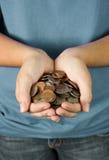 Un adolescente que sostiene un puñado de monedas Foto de archivo