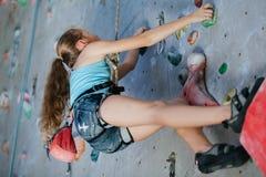 Un adolescente que sube una pared de la roca interior Imágenes de archivo libres de regalías