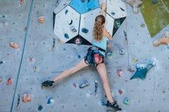 Un adolescente que sube una pared de la roca interior Foto de archivo