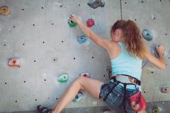 Un adolescente que sube una pared de la roca interior Imagen de archivo