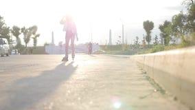 Un adolescente romántico adentro patina sobre ruedas el patinaje en el camino - puesta del sol almacen de metraje de vídeo