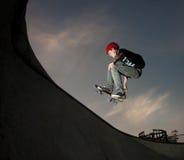 Un adolescente salta del tubo del monopatín Imagen de archivo