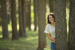 Un adolescente se coloca en un árbol en el parque Fotografía de archivo libre de regalías