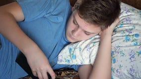 Un adolescente se está acostando y está hojeando la tableta almacen de video