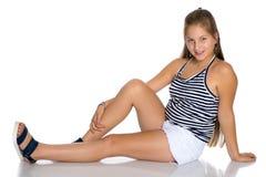 Un adolescente se está sentando en el piso Fotografía de archivo libre de regalías