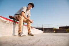 Un adolescente se está sentando en un monopatín en el parque y la sonrisa Imagenes de archivo