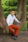 Un adolescente se está sentando en un árbol marchitado en el parque Fotos de archivo libres de regalías