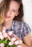 Un adolescente sonríe con los abedules Presentación contra un fondo de la pared de ladrillo con un ramo de tulipanes Foto de archivo