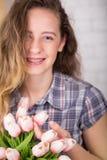 Un adolescente sonríe con los abedules Presentación contra un fondo de la pared de ladrillo con un ramo de tulipanes Foto de archivo libre de regalías