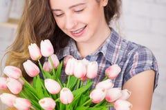 Un adolescente sonríe con los abedules Presentación contra un fondo de la pared de ladrillo con un ramo de tulipanes Imagenes de archivo